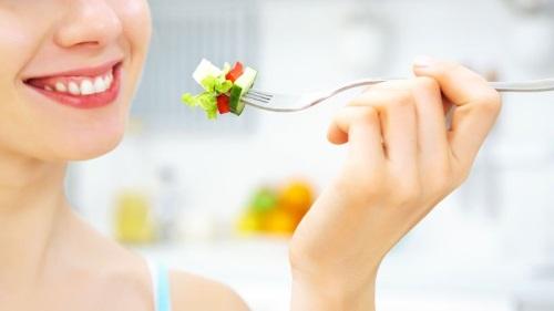 Femme qui mange des légumes à la fourchette